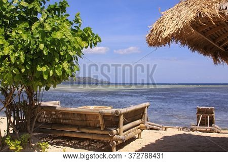 Tropical Straw Umbrella And Sofas With Pillows At Beach Bar On Sunny Exotic Beach Overlooking Low Ti