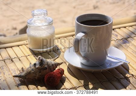 Coffee, Sugar, Shell And Coral On Table On Sunny Tropical Beach In Daylight, On Gili Air Island, Lom