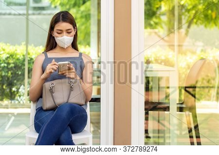 Asian woman customer wear face mask using her mobile phone while sit in waitting social distance queue in front of restaurant with free copyspace for editing. New normal restaurant concept.