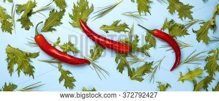 Red Chili Peppers And Green Rucola Salad Leaves On Blue Background.