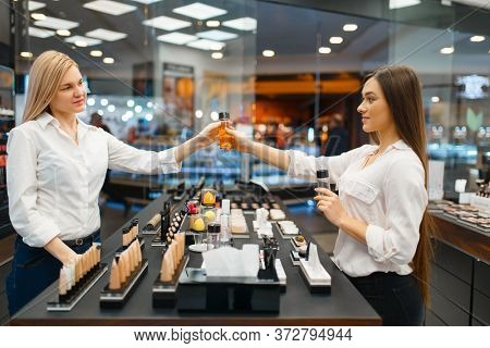 Cosmetician at counter and woman, cosmetics store