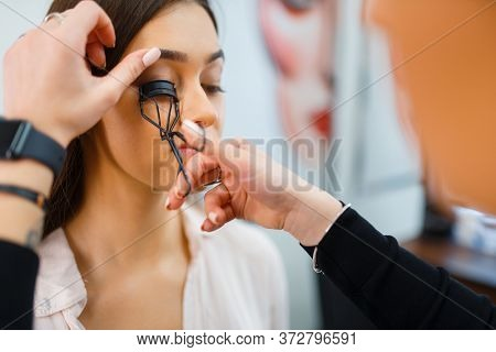 Cosmetician works with woman's eyelashes in store