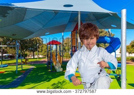 Energetic boy in white suit is engaged in judo. Cosy children 's playground with a variety of multicolored attractions. The concept of physical and mental development of children