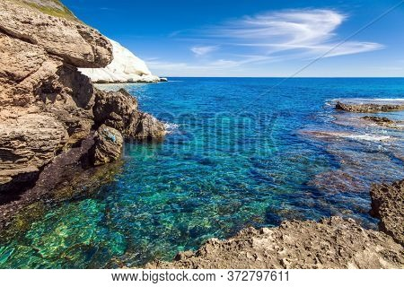 Rocky lagoon near chalk mountain Rosh a Nikra in northern Israel. The border between Israel and Lebanon. The color of sea water from azure to dark blue. The concept of eco and photo tourism
