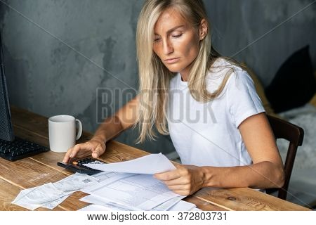 Young Pleasant Blonde Sits At A Table And Counts On A Calculator Bills.  Housekeeping, Payment Of Bi