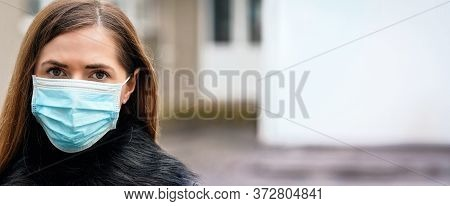 Young Woman Wearing Disposable Blue Virus Face Mouth Nose Mask, Closeup Portrait - Wide Banner With