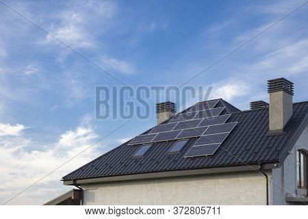 Solar Panel On A Black Roof With Two Chimney Against Cloudy Blue Sky. Energy Saving Image