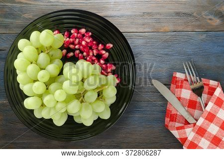Grapes, Pomegranate On A Blue Wooden Background. Grapes, Pomegranate On A Black Plate With Fork And