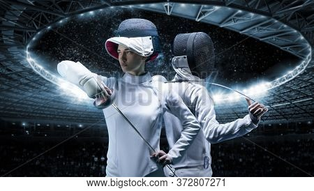 Portrait Of Two Fencers Against The Backdrop Of A Sports Arena. The Concept Of Fencing. Duel.