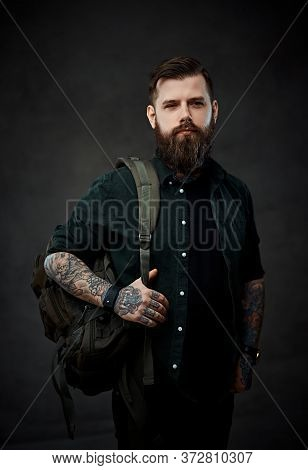 Stylish Bearded Young Man With Tattooed Body Holding Backpack In A Dark Studio.