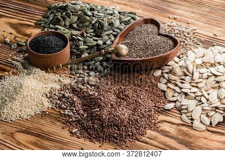 Healthy Seed Collection Set Chia Seeds, Pumpkin Seeds And Sesame Seeds On A Wooden Background