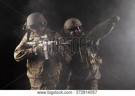 Army Of America. Two Soldiers In Military Equipment With Weapons Stand On A Black Background, A Spec