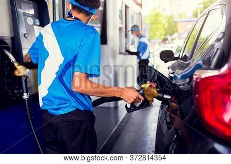 Selective Focus To Petrol Pump Filling Nozzles With Hand Of Staff At The Gas Station. Staff Is Refil