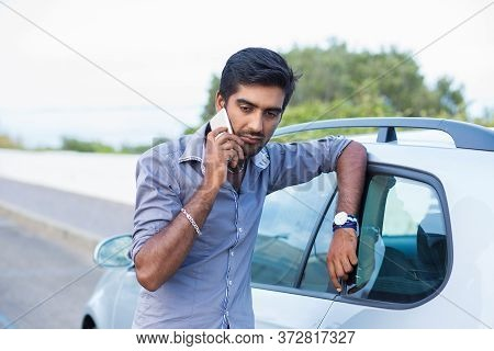 Man Talking On A Cell Phone Leaning On The Door Of His Car Angry Unhappy Sad Displeased With The Con