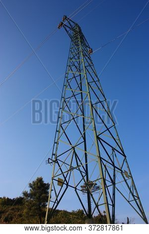 High Electricity Transmitting Antenna In High Voltage Metal Pole In The Woods And Blue Sky