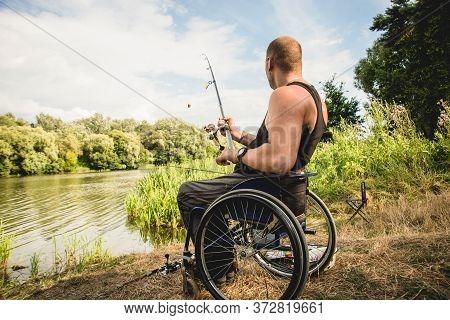 Handicapped Man Fishing At A Lake. Wheelchair Camping.