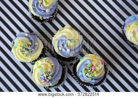 Top view of yellow and lilac cupcake on a black and white lined background