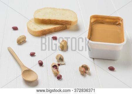 Peanut Paste, White Bread And Peanut Fruit On A White Table. Natural Peanut Cream.
