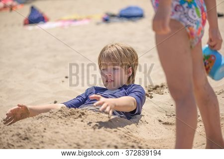 Portrait Of A Boy Playing On The Beach Buried In The Sand