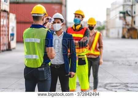 Professional Of Group Cargo Foreman In Helmets Standing And Using Infrared Thermometer For Checking