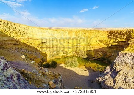 View Of A Water Hole And Layered Rock Formation, Along The Ramon Colors Route, In Makhtesh Ramon (ra