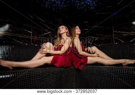 Two Beautiful Girls In A Red Bath Towel On On A Stone Bench At Sauna With Black Walls. Woman Who Is