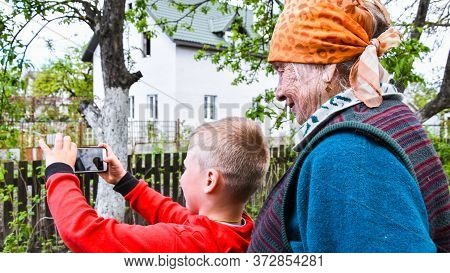 Happy Grandmother And Grandson Taking Selfie Photo. Concept Of Happy Family, Video Call In Home Gard