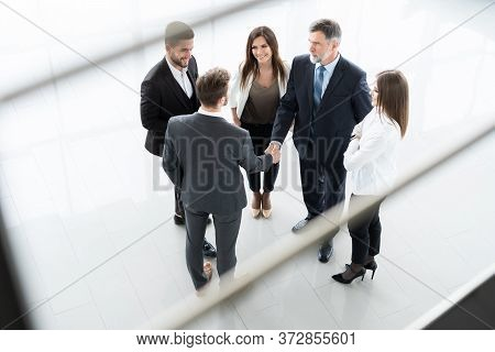 Top View Of Business People Shaking Hands, Finishing Up A Meeting - Welcome To Business.