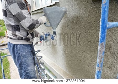 A Building Contractor Is Rendering, Plastering, Coating The Exterior Wall Of A Building Using Plaste