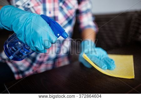 Cleaning Dark Table Surface With Spray Detergent, Blue Rubber Gloves And Yellow Dish Cloth On Work S