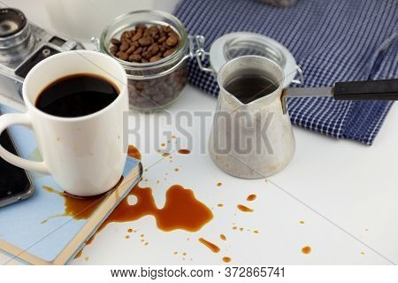 Coffee Spilled On A Book On The Desktop. A Cezve For Coffee, Coffee Beans, A White Cup Of Coffee, Sp