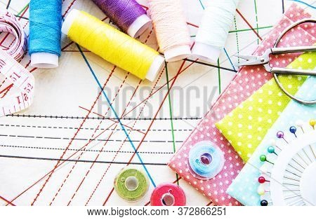 Sewing Accessories And Fabric On A Table. Sewing Threads, Needles, Pins, Fabric, Buttons And Sewing