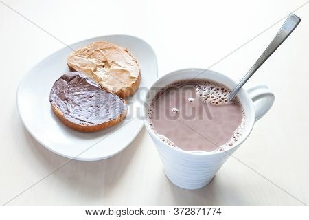 Above View Of Cup With Cocoa And Toasts With Peanut Butter And Chocolatte And Hazelnut Spread On Pla
