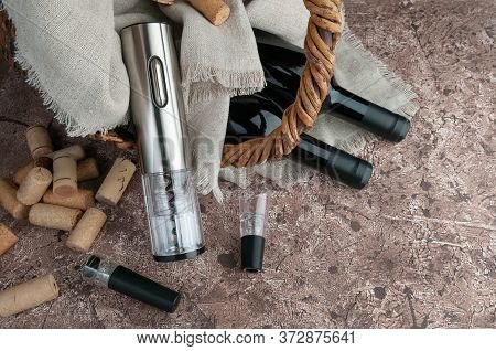 Gray Electric Corkscrew Made Of Metal. It Stands Next To A Basket In Which Two Bottles Of Wine. Near
