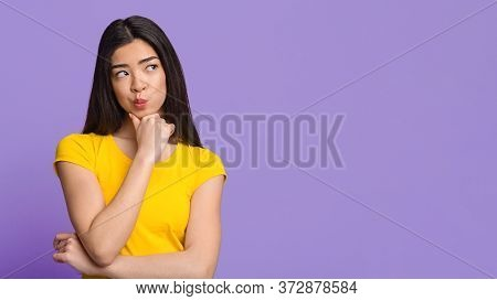 Doubtful Choice. Pensive Asian Woman Touching Ching And Looking At Copy Space On Purple Background,
