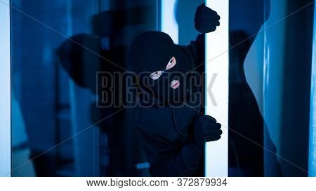 Intrusion Concept. Villain With Black Hat Sneaking Into Apartment, Lurking Out Open Glass Door, Bann