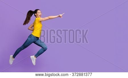Look There. Excited Asian Girl Jumping And Pointing Aside At Copy Space On Purple Background, Full-l