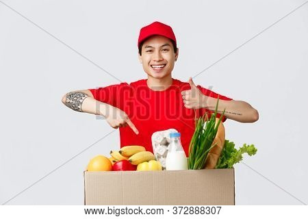 Online Shopping, Food Delivery And Internet Stores Concept. Smiling Friendly Courier In Red T-shirt