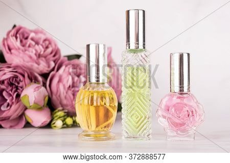Different Transparent Perfume Bottles With Bouquet Of Peonies On Light Marble Background. Aromatic E