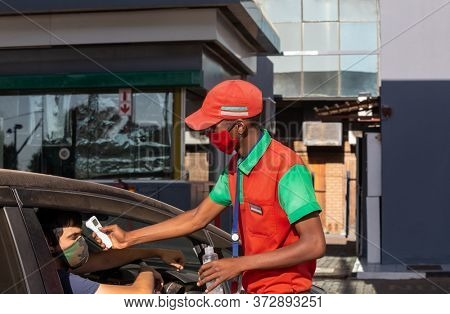 African attendant at a gas station checking the driver temperature with an infrared thermometer