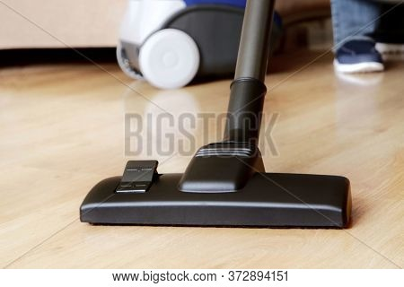 Close-up  Modern Vacuum Cleaner  Over  Wooden Parquet Floor Background.vacuuming, Housekeeping And C