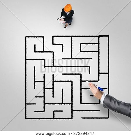 Top View Of Puzzled Businesswoman In Helmet Looking At Drawn Maze On Floor