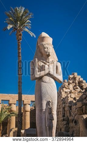Mighty stone statue of Luxor Temple in Luxor, ancient Thebes, Egypt. Luxor Temple is a large Ancient Egyptian temple complex located on the east bank of the Nile River