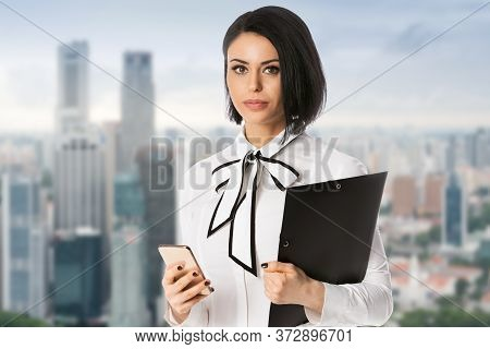 Business Woman Holding Phone And Black Folder With Documents In Hands Over City Background. Concept