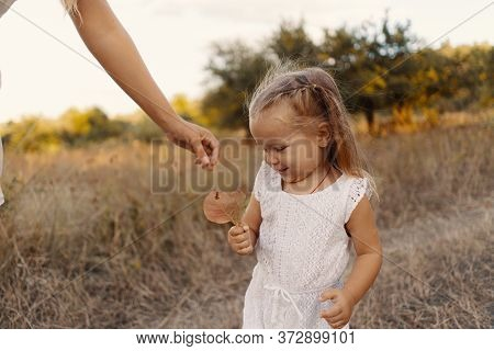 Smiling Lovely Girl Watching With Enthusiasm Lives Given By Her Mothers Hand. Mother Playing With He