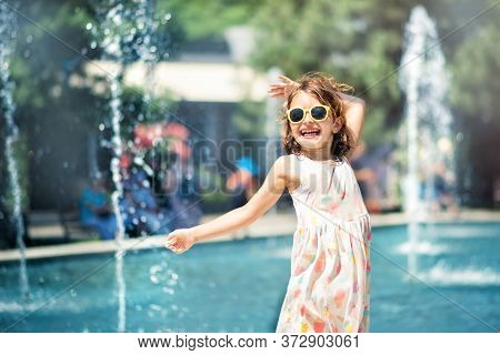 Loving Life. Cheerful Little Girl In Summer Light Dress And Yellow Sunglasses Having Fun And Dancing