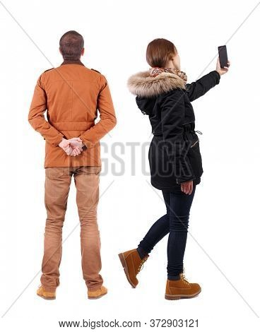 Back view of couple in winter jacket photographed on a mobile phone in winter jacket. Rear view people collection. backside view of person. Isolated over white background.