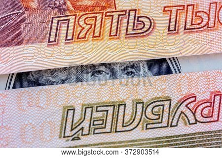 Eyes Of George Washington On 1 Dollar Bill Banknote Looking Through Russian Paper Rubles Banknotes.