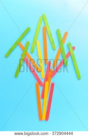 A Tree Made With Colorful Wood Sticks On A Blue Background. Creative Design.