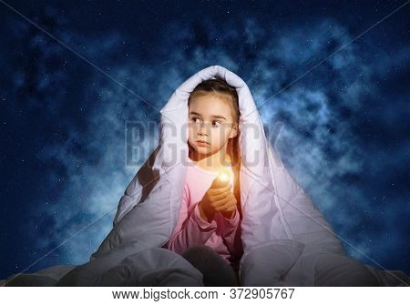 Frightened Girl With Flashlight Hiding Under Blanket. Scared Kid Lying In His Bed At Home. Fear Of T